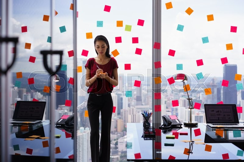 Stock image of 'Mixed race secretary working in modern office in skyscraper, writing and sticking adhesive notes with tasks on window. '
