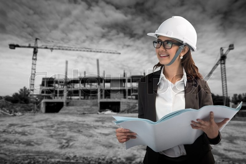 Stock image of 'Women construction, architecture, building and people concept - smiling girl in protective helmet with clipboard and blueprint'