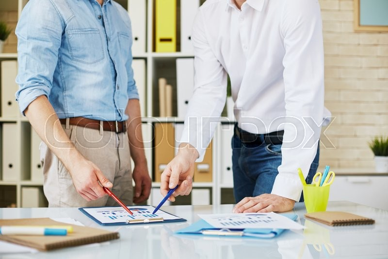 Stock image of 'Professional businessmen discussing together  financial report and pointing at charts'