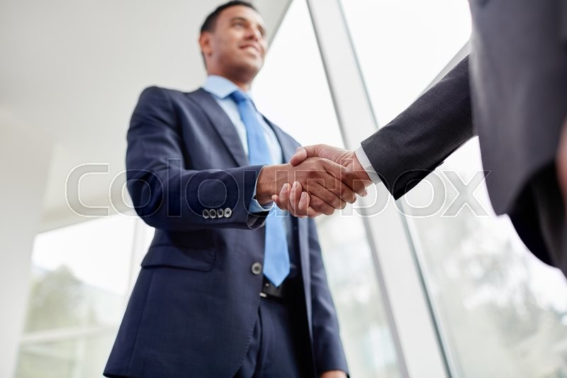 Stock image of 'Businessmen shaking hands at the office'