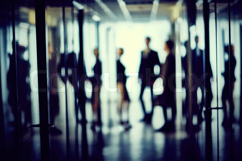 Stock image of 'Blurred silhouettes of managers in office center'