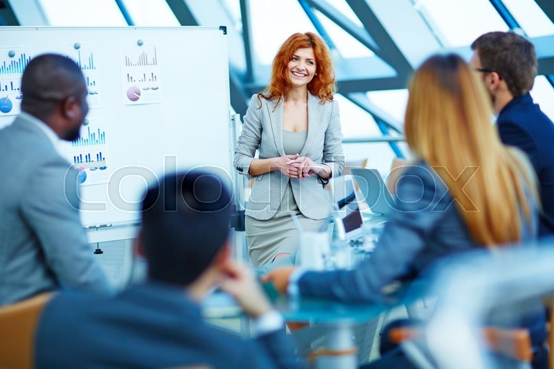 Stock image of 'Smiling businesswoman presenting business project to her partners'