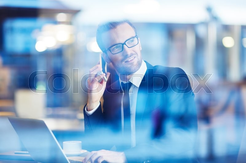 Stock image of 'Young businessman speaking on the phone in cafe'