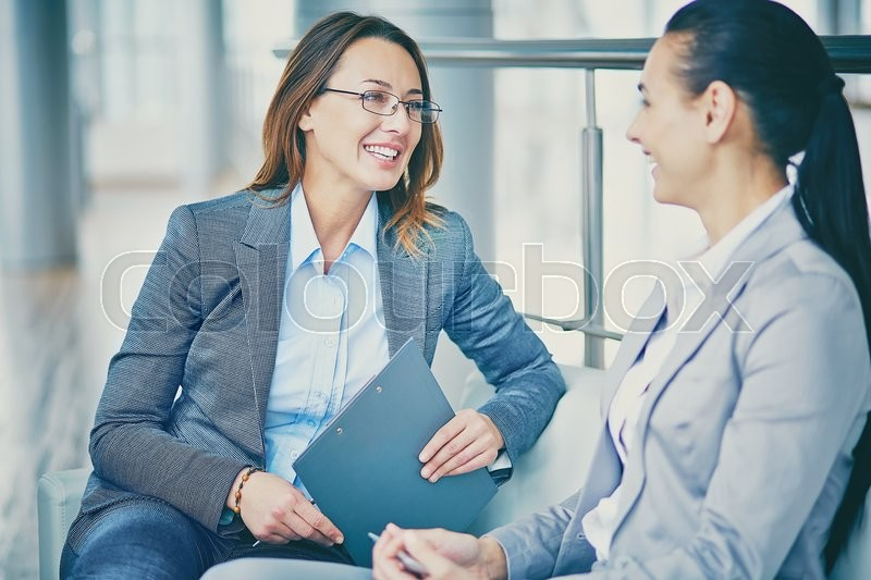 Stock image of 'Two businesswomen discussing their ideas at break'