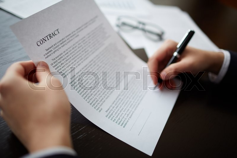 Stock image of 'Close-up of male hands signing a contract with pen'
