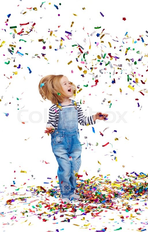 Stock image of 'Ecstatic girl playing with confetti while standing on the floor'