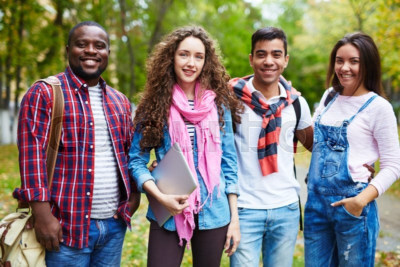 Stock image of 'Joyful college friends in casualwear standing outside'