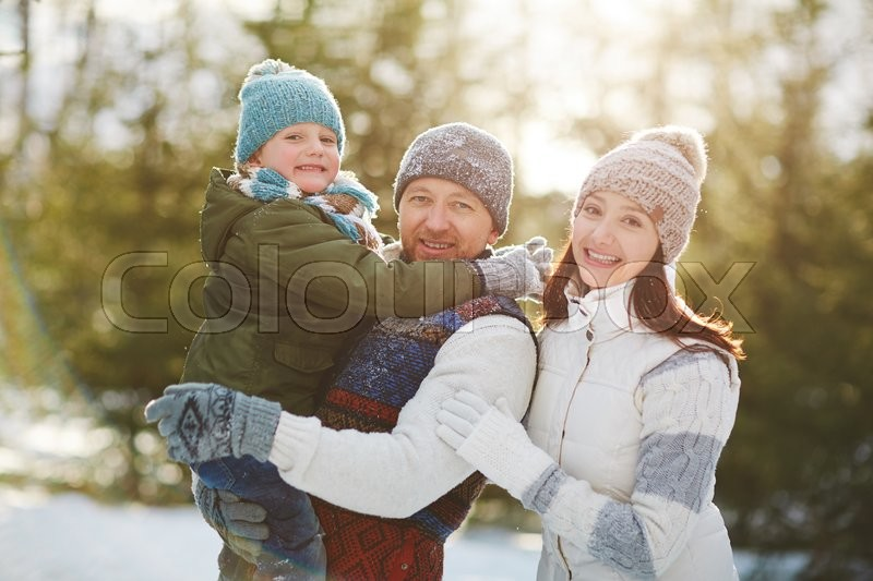 Stock image of 'Happy family walking outdoors with their child'