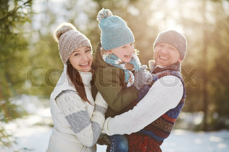 Stock image of 'Joyful family of three looking at camera in winter park'