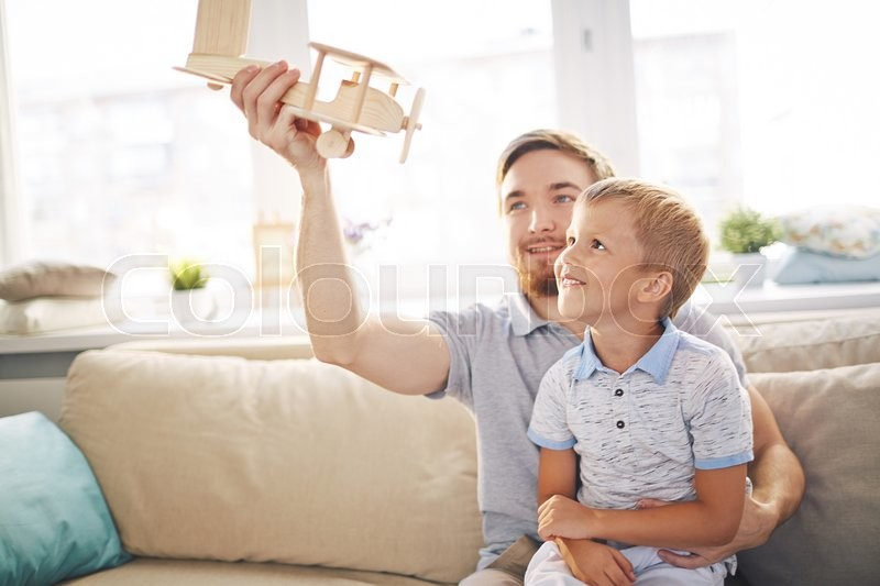 Stock image of 'Young father playing with his son on sofa'
