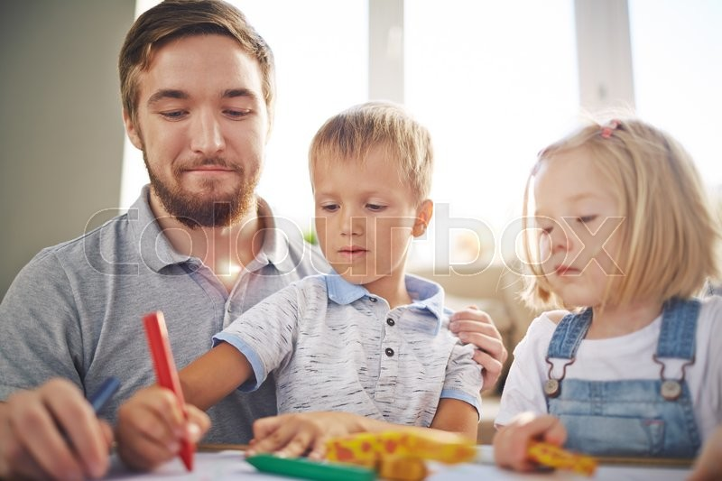 Stock image of 'Young man and little girl looking at cute boy drawing'