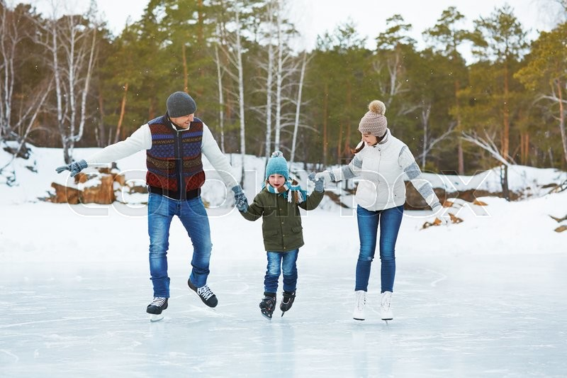 Stock image of 'Happy parents with son skating on the rink'