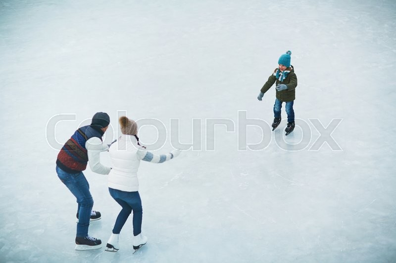 Stock image of 'Little boy on skates standing on the rink and looking at his parents'