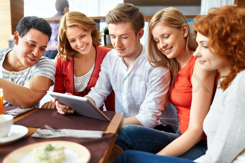 Stock image of 'Friends with touchpad networking in cafe'