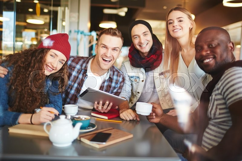 Stock image of 'Multi-ethnic teenagers looking at camera in cafe'