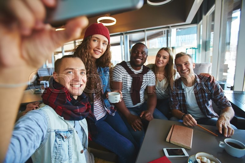Stock image of 'Teenage friends making selfie while gathering in cafe'