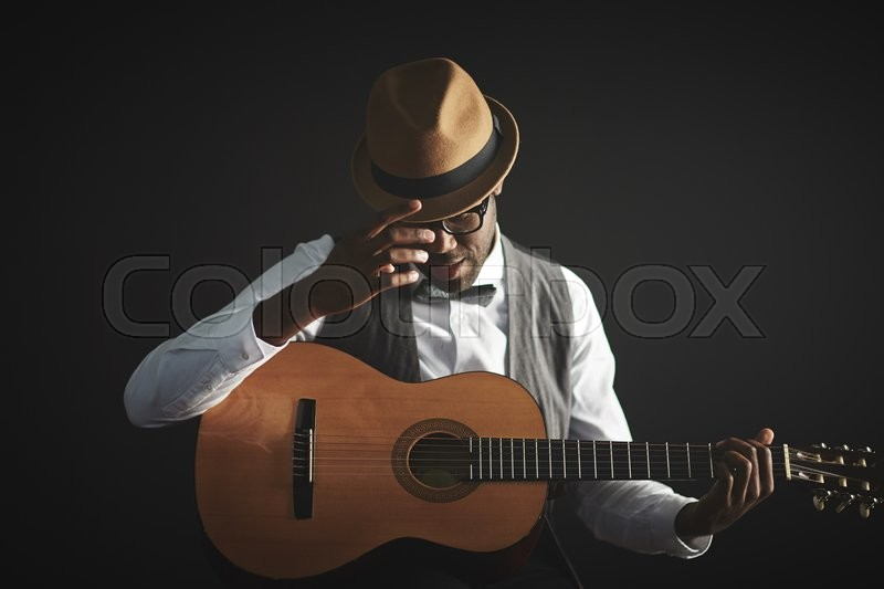 Stock image of 'Elegant young man in smart clothes and hat holding guitar'