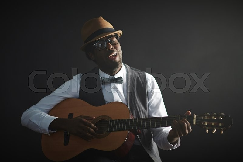 Stock image of 'African young man playing guitar and singing'