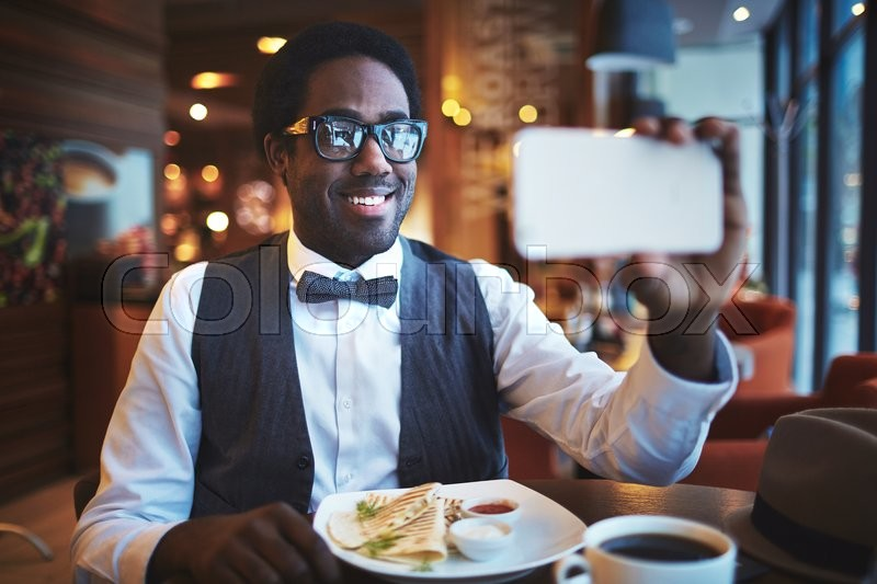Stock image of 'Elegant young man making selfie while sitting in cafe'