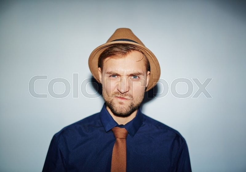 Stock image of 'Confused or annoyed guy in hat, tie and shirt looking at camera'