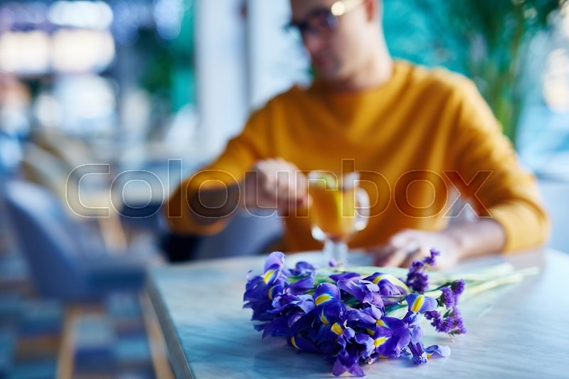 Stock image of 'Close-up of flowers on the table with man waiting his girlfriend behind'