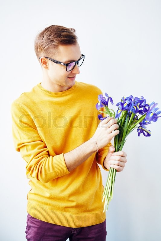 Stock image of 'Handsome man holding bunch of fresh blue irises'