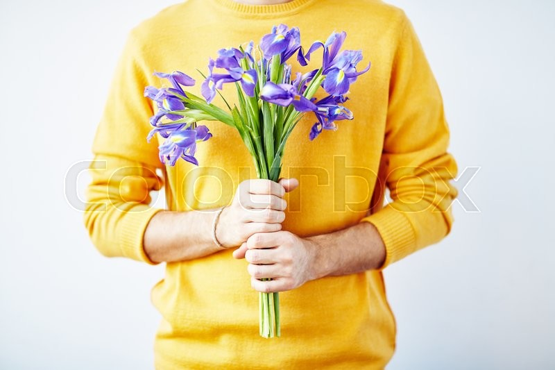 Stock image of 'Hands of guy with bouquet of blue irises'