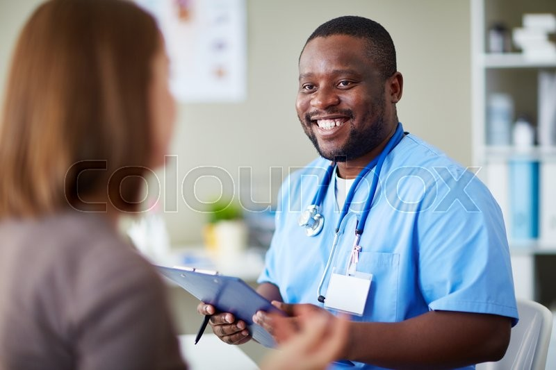 Smiling African doctor working with patient in his office, stock photo