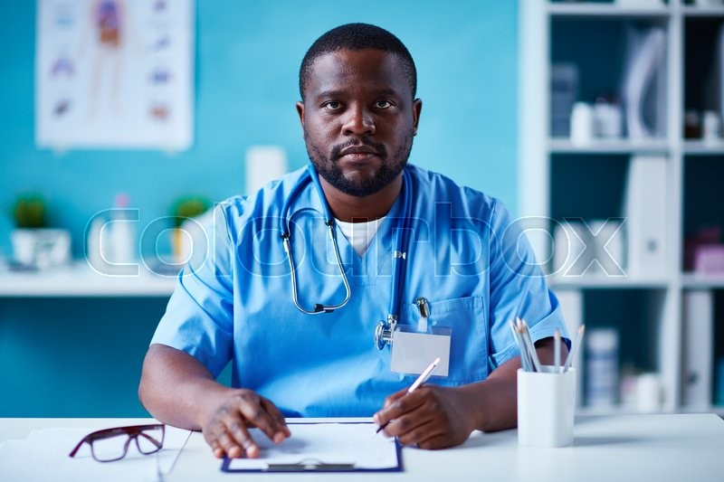 Stock image of 'Young clinician in uniform looking at camera while making notes'