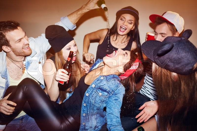 Stock image of 'Ecstatic friends pouring beer into girl mouth at swag party'