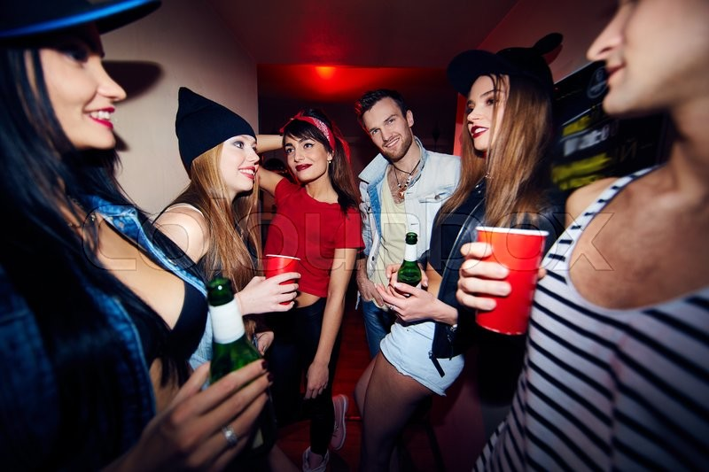 Stock image of 'Young stylish people with drinks gathering in bar'