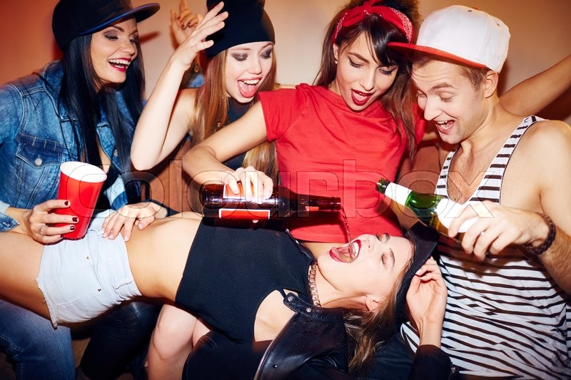 Stock image of 'Ecstatic friends pouring beer into girl mouth in bar'