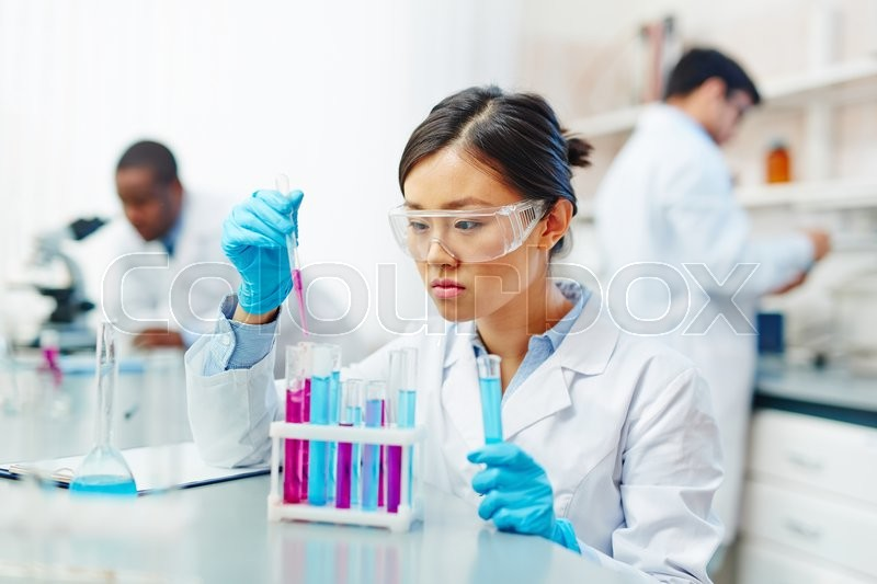 Stock image of 'Young scientist making experiment with liquid substances in flasks'