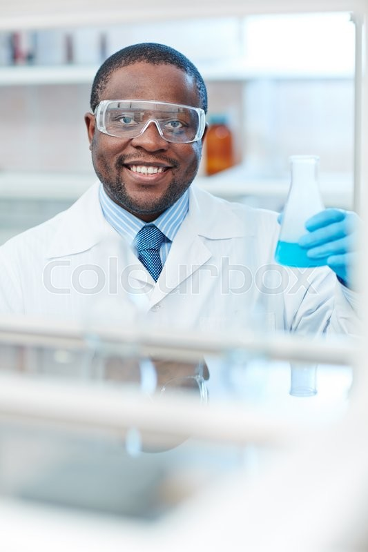 Stock image of 'Happy laboratory worker with tube looking at camera'
