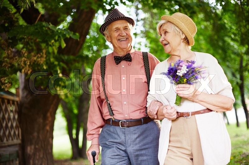 Stock image of 'Happy senior couple enjoying walk in park'