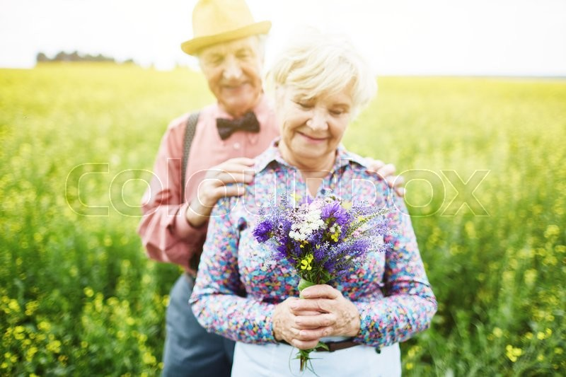 Stock image of 'Happy senior woman with bunch of wildflowers and her husband behind'