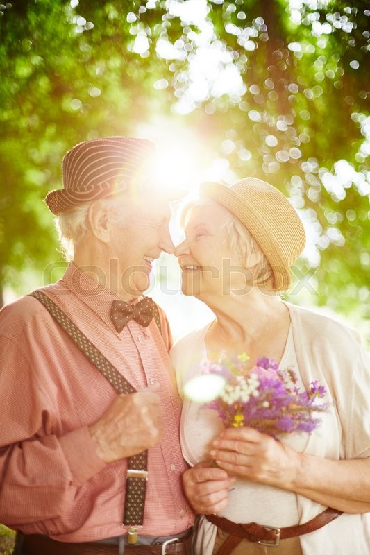 Stock image of 'Flirty seniors looking at one another on sunny day'