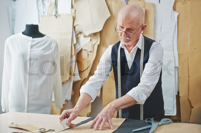 Stock image of 'Mature tailor cutting out pattern in tailoring shop'