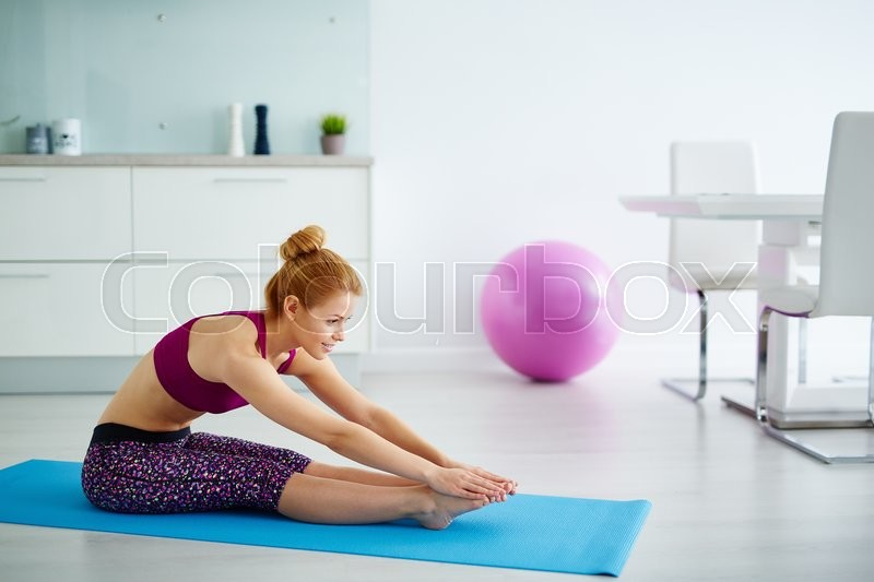 Stock image of 'Young woman sitting on mat and doing stretching exercise'