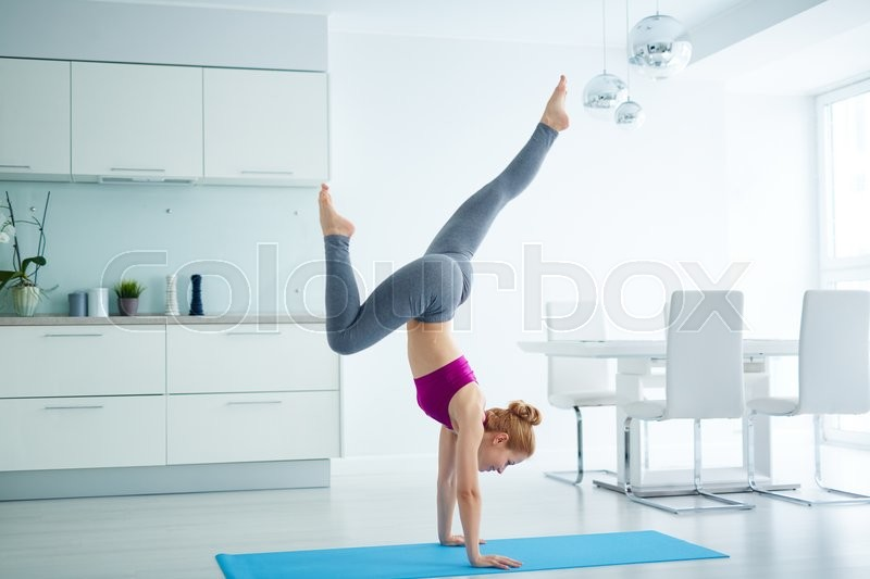 Stock image of 'Young active woman doing exercise for balance on mat'