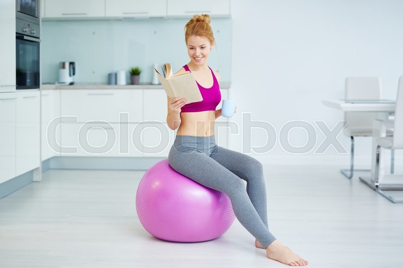 Stock image of 'Young active woman with cup of tea and book sitting on fitness ball in the kitchen'