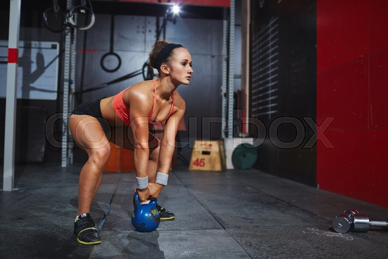 Stock image of 'Strong female working out with heavy barbell in gym'