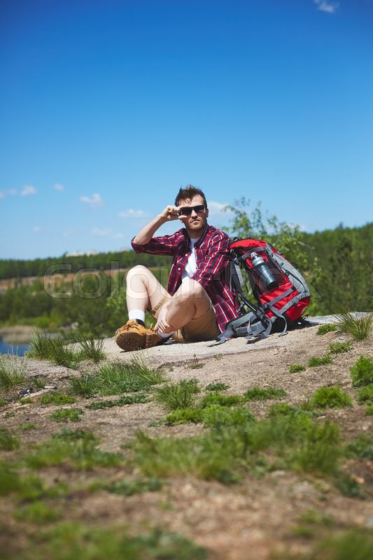 Stock image of 'Young hiker with backpack sitting by lake'