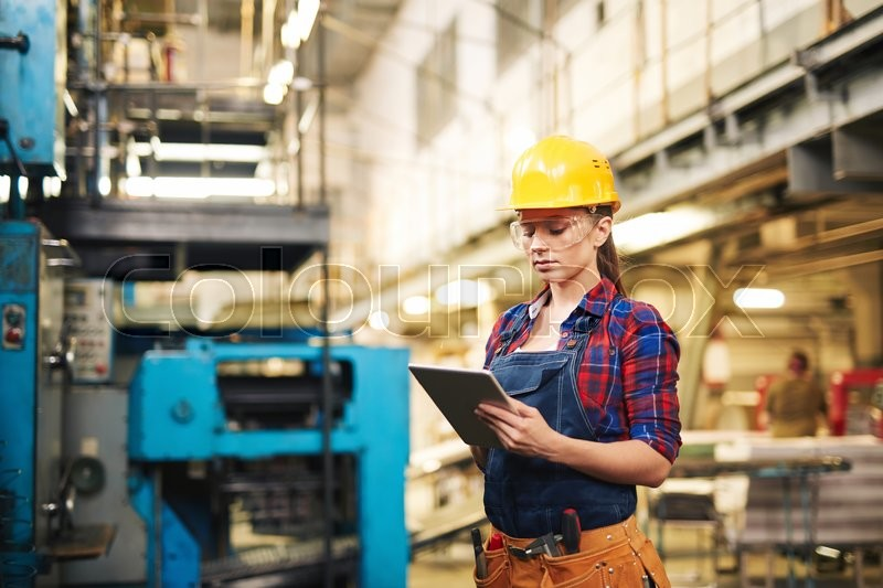 Stock image of 'Woman in protective clothing using touchpad in factory'