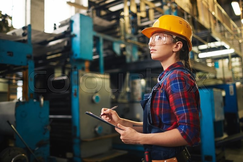 Stock image of 'Modern female worker in uniform and helmet working at plant'