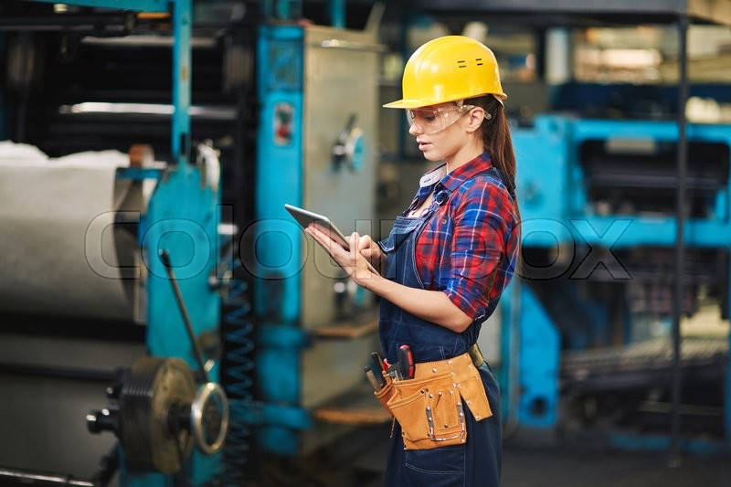 Stock image of 'Manufacturing worker using digital tablet at work'