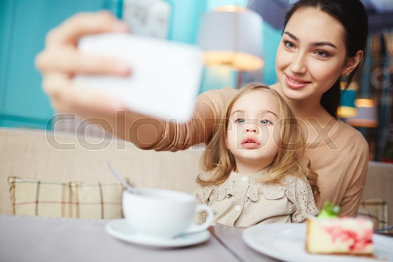 Stock image of 'Young woman making selfie of herself and her little daughter in cafe'