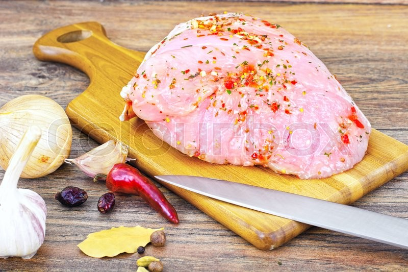 Stock image of 'A Piece of Raw Turkey in Spices for Grilling on Woody Background Studio Photo'
