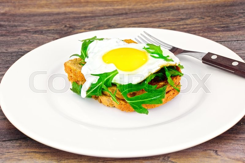 Stock image of 'Scrambled Eggs with Arugula on Whole Grain Bread Health Food'