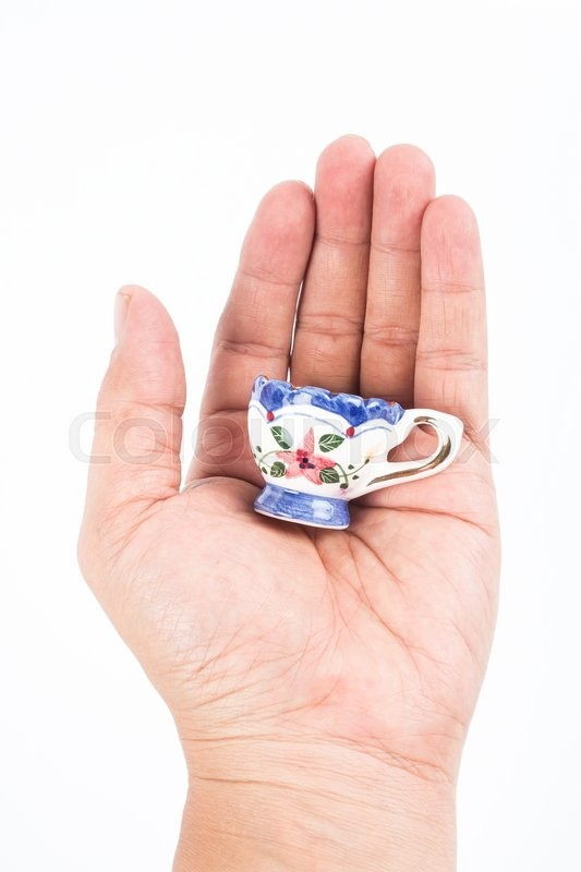Stock image of 'small ceramic cup in hand on white background'